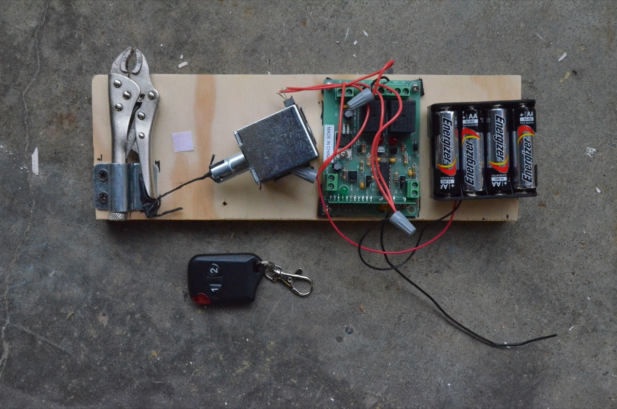 A self-contained unit containing vise grips, solenoid, remote control receiver and battery pack was activated by a remote control to release the curtain.