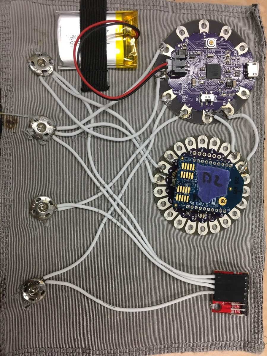 """The """"brain"""" of the interface: An Arduino Lilypad, Xbee radio, battery, gyro sensor, and the four snaps that connect the brain to the garment and make electrical connections to the I2C network."""