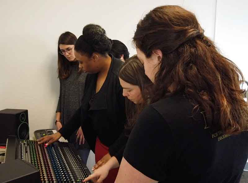 Students learn signal flow on Mackie consoles at Women's Audio Mission