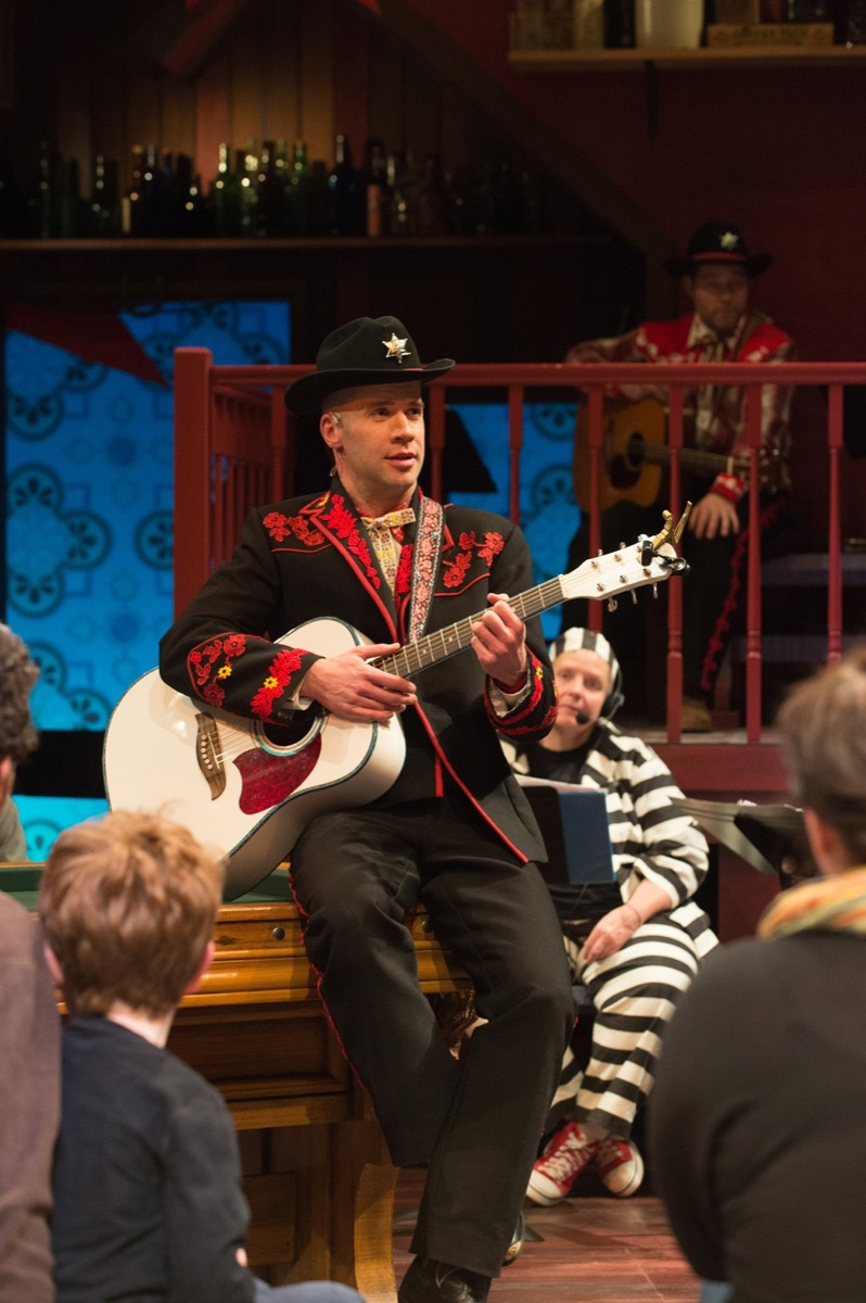 Jeremy Peter Johnson performs in Yeomen of the Guard, while Amy T. Hutcheson, stagehand supervisor (in striped prison guard costume), watches the action, and the crowd.