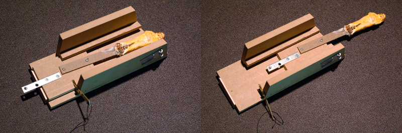 The sled fully retracted in the track, at left, and the sled when extended, at right. This whole unit (plus the surgical tubing) was mounted to the back of the flat, where a hole was cut just large enough for the fake knife handle to fit through.