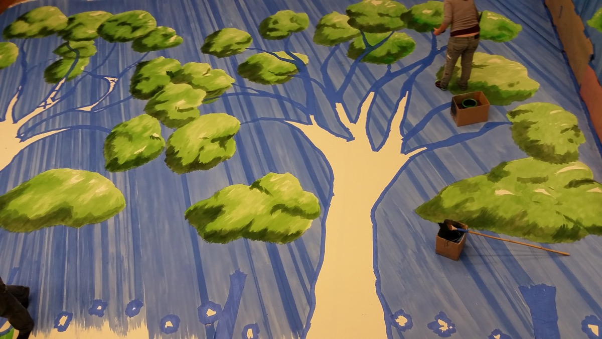 A scenic artist at the Colorado Springs Fine Arts Center paints trees for the backdrop, with certain parts of the drop still masked off.