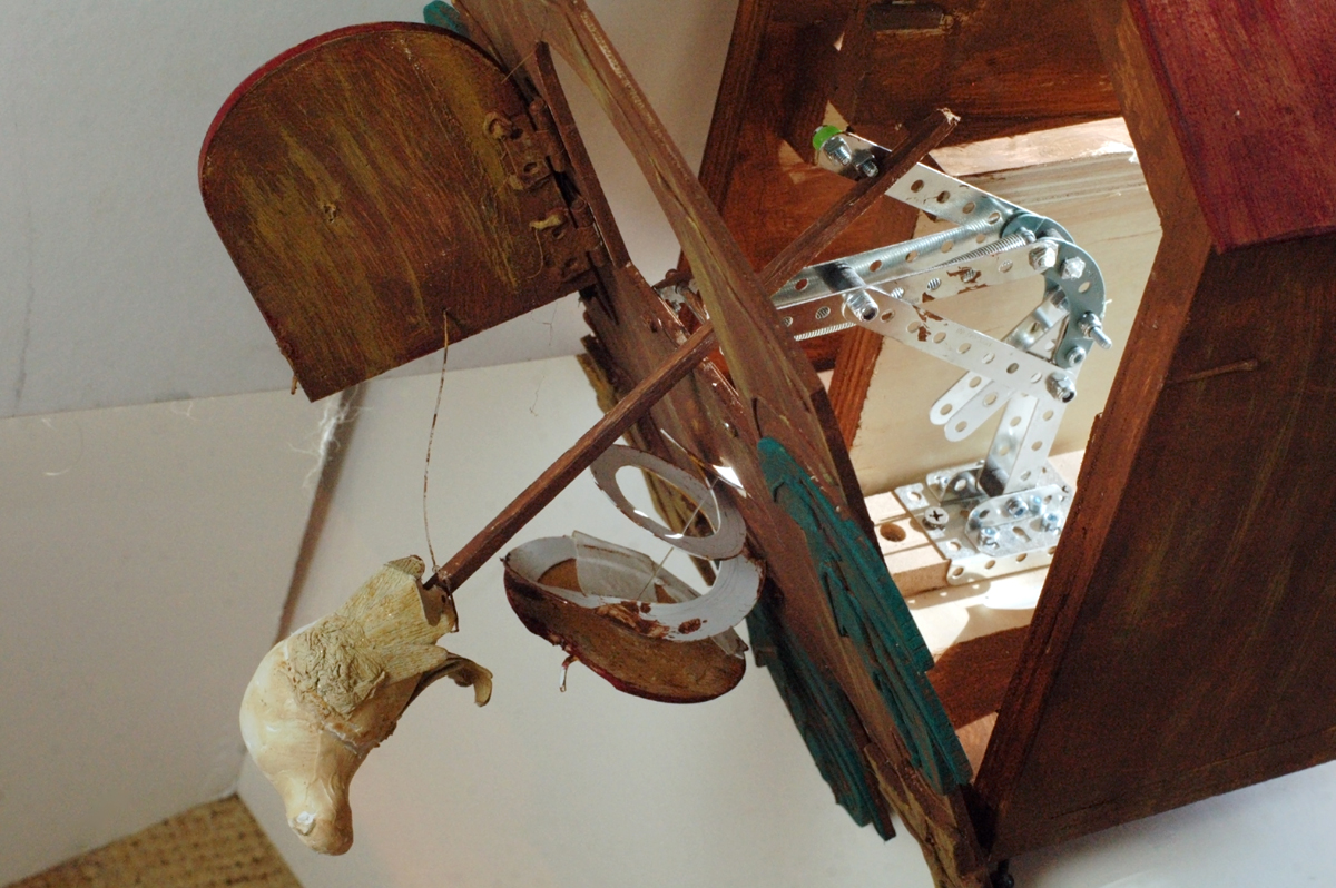 The prototype of the cuckoo clock with the front of the clock open, and the bird pushed through its door.