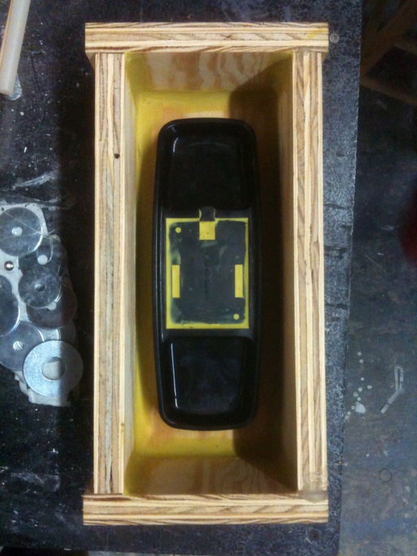 To make a mold of a phone, we placed a real base of a phone in a box, and poured silicon rubber over it.