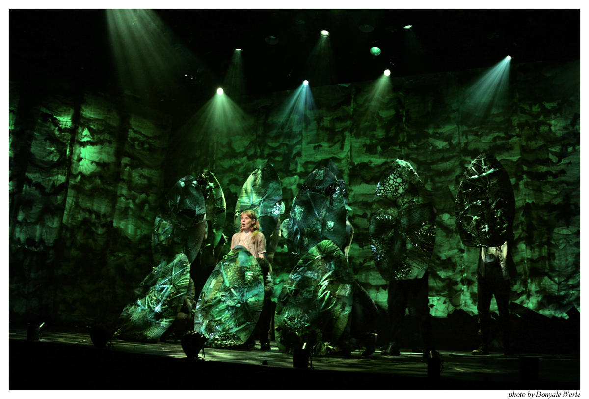 """A moment from the Broadway production of Peter and the Starcatcher, with """"Jungle Board"""" hand props in use."""
